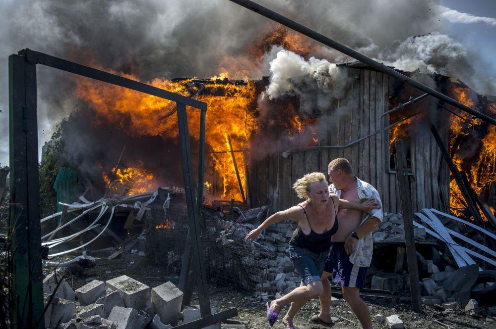 Lugansk bölgesinde yerel sakinler yangından kurtulmaya çalışıyor.