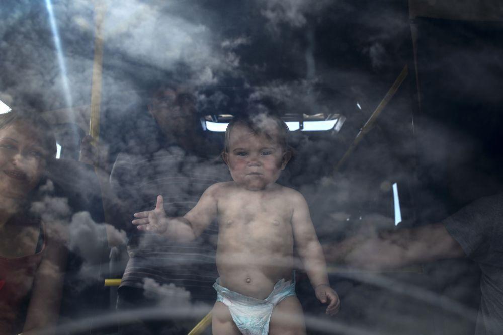 Lugansk bölgesinde İzvarino sınır kapısında bekleyen otobüsteki çocuk.