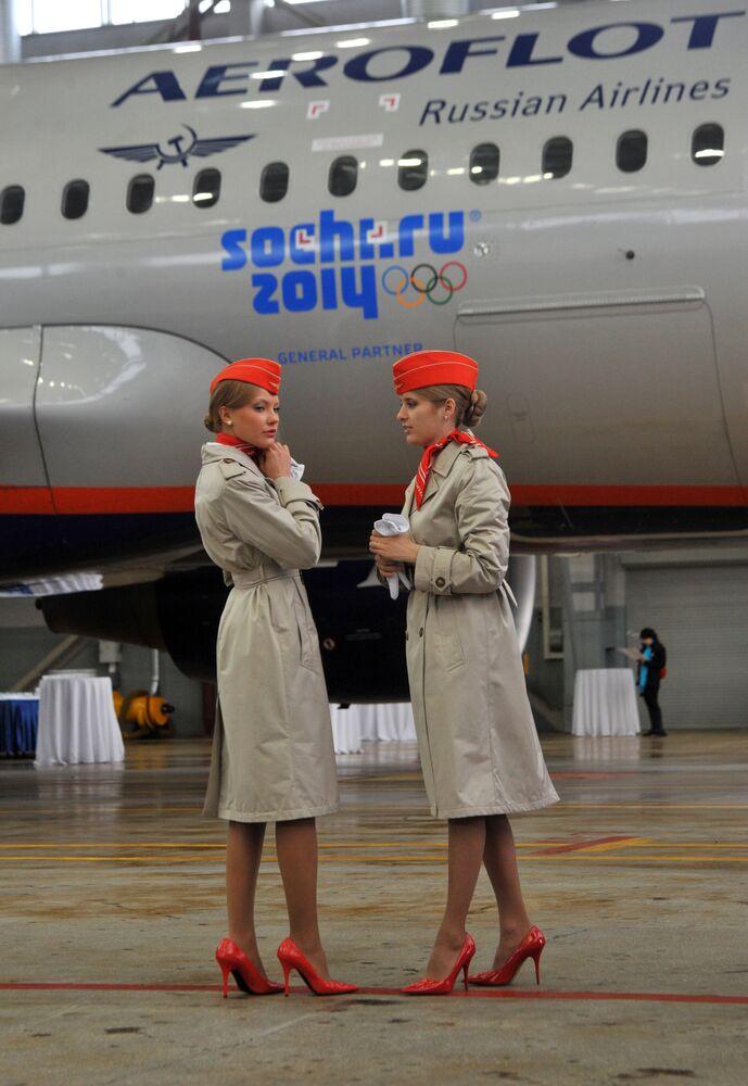 Aeroflot hostesleri, 2014 Soçi Olimpiyatları sembolleriyle süslü uçağın önünde.