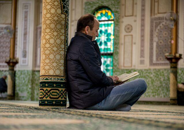 Brüksel'deki Büyük Camii'de Kuran okuyan bir kişi