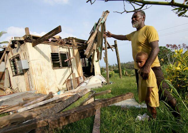 Tailevu bölgesinde Winston kasırgasının yıktığı evinin önünde poz veren bir Fijili