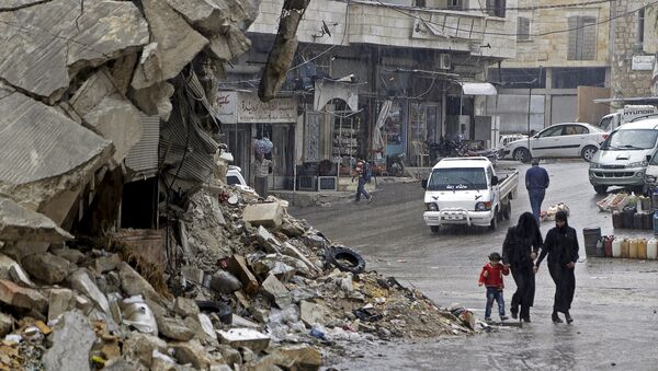 Civilians walk in the rain past a damaged building in the rebel-controlled area of Maaret al-Numan town in Idlib province, Syria October 28, 2015 - Sputnik Türkiye