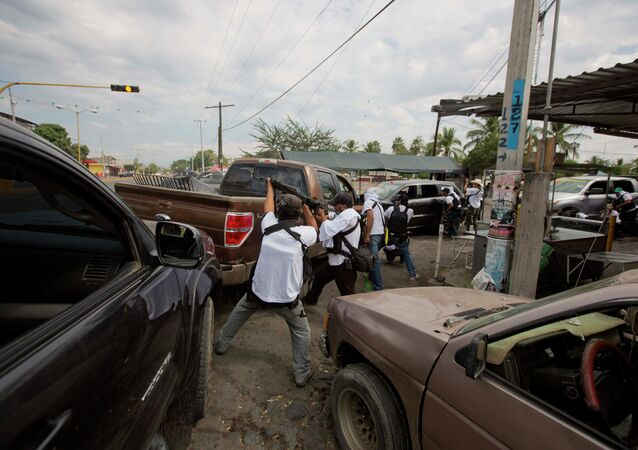 In this Jan. 12, 2014 file photo, the Self-Defense Council of Michoacan (CAM) engage in a firefight as they try to flush out alleged members of the Knights Templar drug cartel from Nueva Italia, Mexico