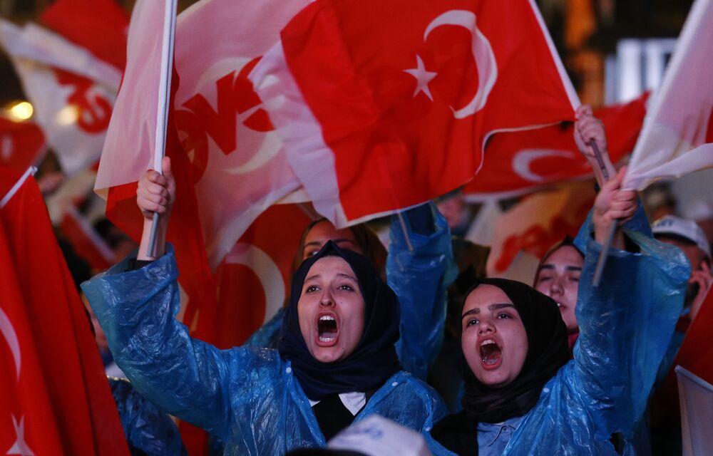 Türk bayrakları, AK Parti ve üzerinde evet yazan bayraklarla AK Parti binaları önüne gelen vatandaşlar, henüz resmi olmayan halk oylaması sonuçlarını kutluyor.