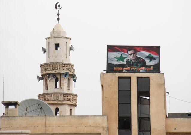 Hama'ya bağlı Suran kasabasında bir caminin yanında bulunan Suriye Devlet Başkanı Beşar Esad'ın fotoğrafının yer aldığı pano