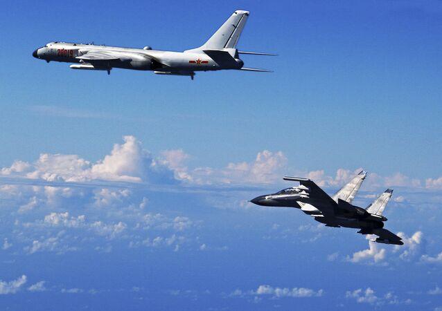 Çin'e ait bir SU-30 jeti  bir H-6K bombardıman uçağıyla birlikte Doğu Çin Denizi üzerinde tatbikatta