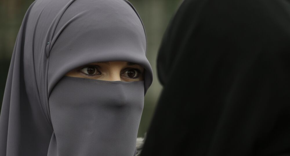 A Muslim woman talks with a friend during events to observe World Hijab Day, celebrating the veil traditionally worn by Muslim women