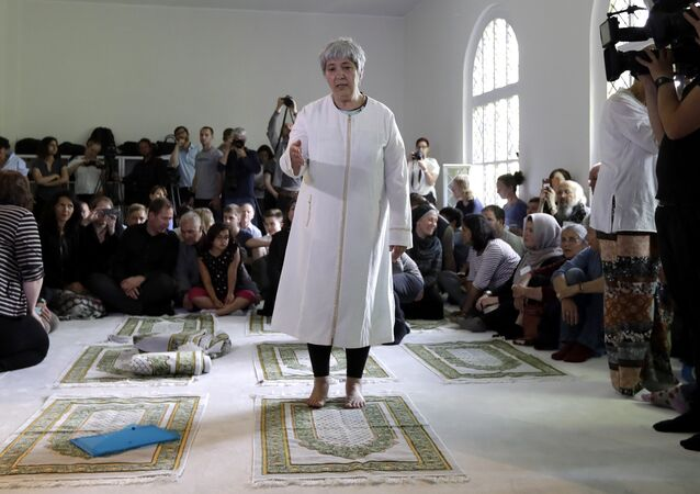Seyran Ates, standing at center, founder of the Ibn-Rushd-Goethe-Mosque gestures during the opening of the mosque in Berlin, Germany, Friday, June 16, 2017