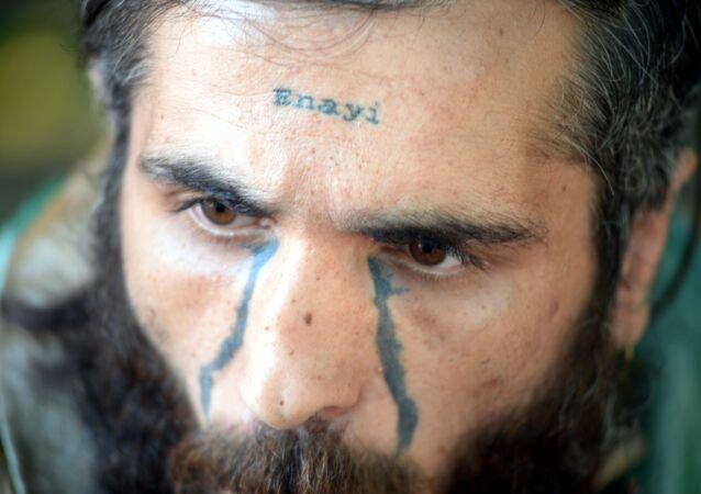Alnında 'enayi' yazan bir dövmesi olan Adem Akkoç