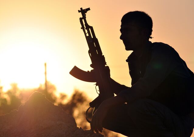 A fighter from the Kurdish People Protection Unit (YPG) poses for a photo at sunset in the Syrian town of Ain Issi, some 50 kilometres north of Raqqa, the self-proclaimed capital of the Islamic State (IS) group during clashes between IS group jihadists and YPG fighters on July 10, 2015