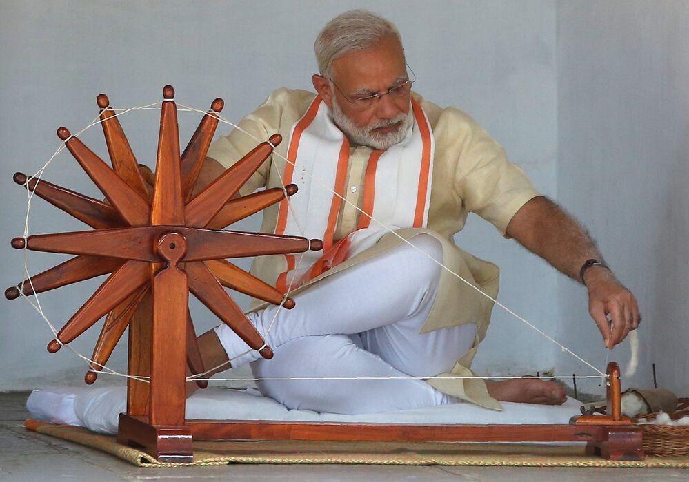 Ahmedabad'daki Sabarmati Aşram'ında Mahatma Gandi'nin kişisel eşyalarını inceleyen Modi, tıpkı Gandi gibi çıkrıkta pamuktan iplik eğirdi.