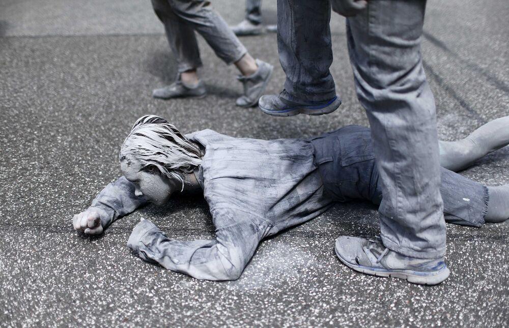 Üzerlerinde gri takım elbiselerle tepeden tırnağa kile bürünmüş protestocular Hamburg sokaklarını arşınladı.