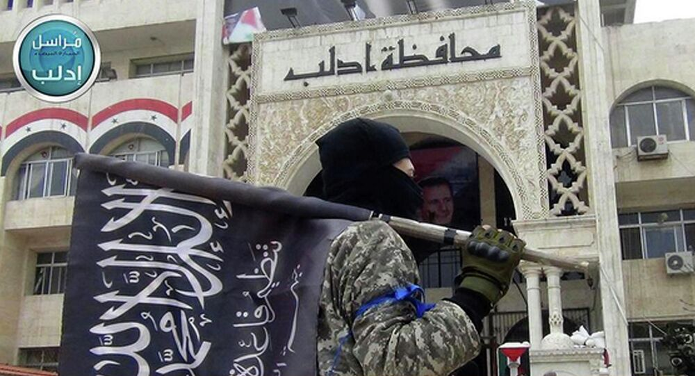 A fighter from Syria's al-Qaeda-linked Nusra Front holds his group flag as he stands in front of the governor building in Idlib province, north Syria.