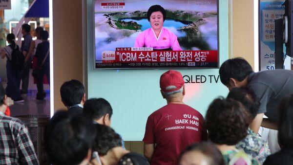 People watch a TV news report about North Korea's hydrogen bomb test at a railway station in Seoul, South Korea on September 3, 2017. - Sputnik Türkiye