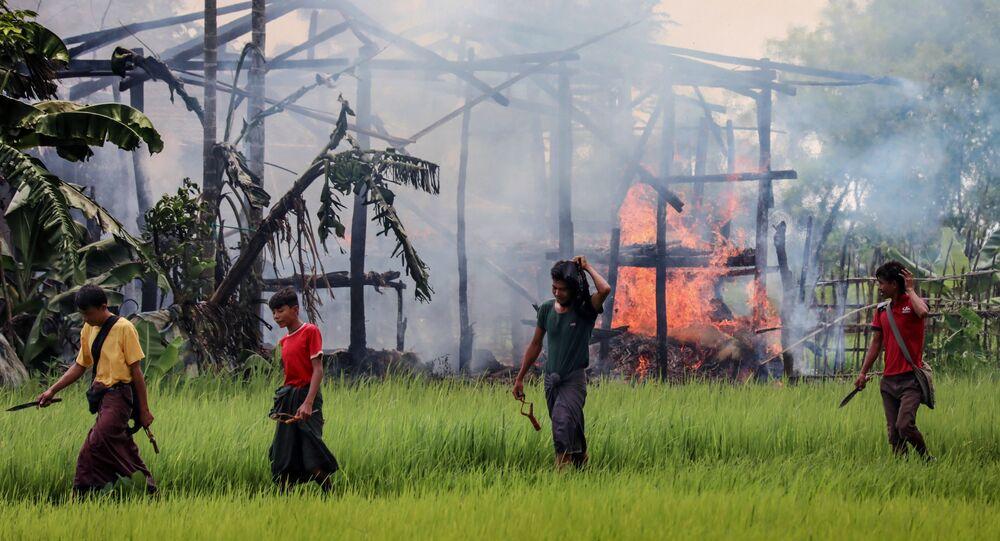 Arakan'da yanan bir evin etrafında dolaşan eli bıçaklı ve sapanlı kimli belirsiz kişiler