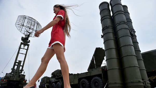 A woman walks near Russia's air defence system S-400 Triumf launch vehicles at the military exhibition - Sputnik Türkiye