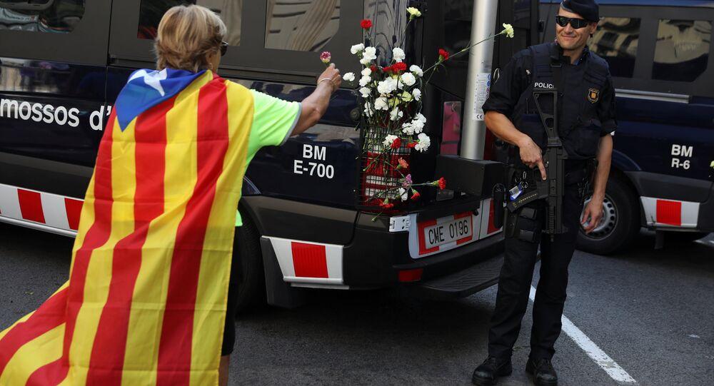 Kataln bayrağı Estalada'yı kuşanan bir bağımsızlık yanlısı İspanyol jandarmasının aracına çiçek bırakıyor