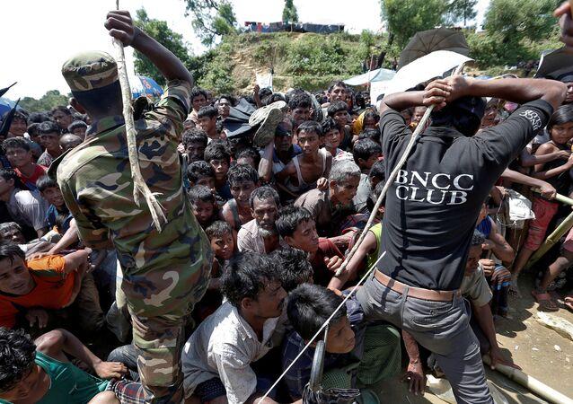Bangladeşli asker ve güvenlik personeli ,Cox Bazar'da Arakanlı sığınmacıları sopalarla sıraya sokuyor
