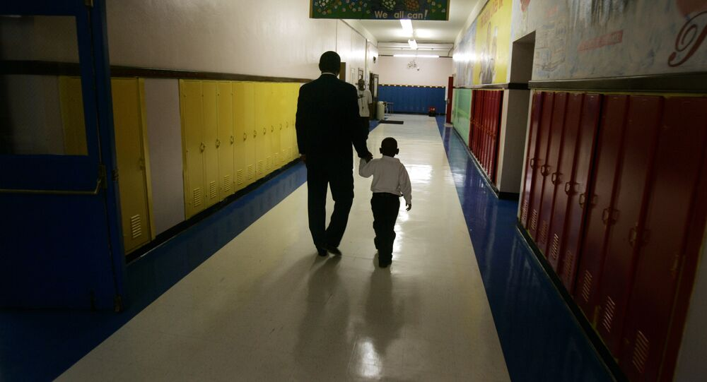 Principal Milton Andrew walks with a kindergarten student to comfort the child during the first day of class at Wilkins Elementary School in Detroit, Thursday, Sept. 14, 2006