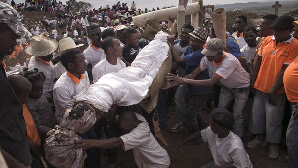 People carry a body wrapped in a sheet as they take part in a funerary tradition called the Famadihana in the village of Ambohijafy, a few kilometres from Antananarivo, on September 23, 2017 - Sputnik Türkiye