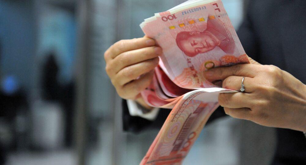 A bank employee counts 100-yuan banknotes at a bank in Hangzhou, east China's Zhejiang province on December 1, 2015.
