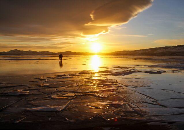İnsanlar, donmuş Baykal Gölü'nün üzerinde dolaşıyor.