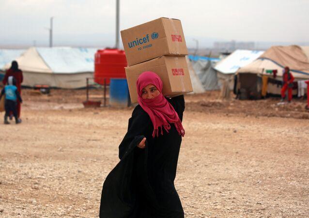 Suriyeli kadın sığınmacı Deyr Ez Zor'dan kaçmış Haseke'deki kampta UNICEF yardım kutularını taşıyor