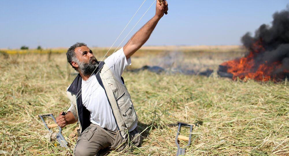 Gazze'de 'Toprak Günü' nedeniyle yapılan gösterilerde sınırdaki İsrail askerlerine taş atan bir Filistinli