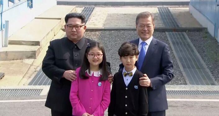 Kuzey Kore ve Güney Kore liderleri görüşme öncesi çocuklarla poz verirken