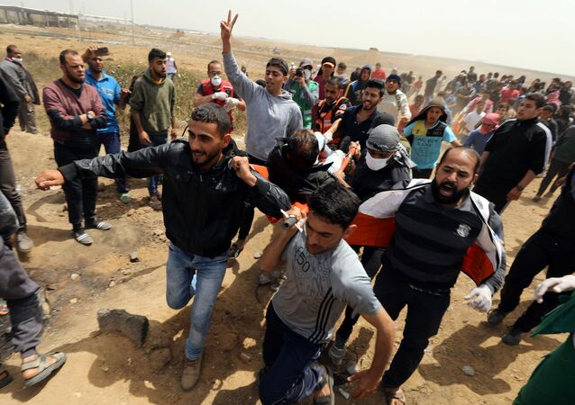 A wounded Palestinian is evacuated during clashes with Israeli troops at a protest demanding the right to return to their homeland, at the Israel-Gaza border, east of Gaza City, April 13, 2018