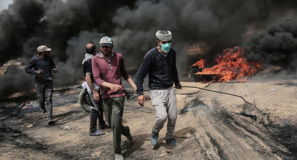 Palestinian protesters pull on a burning tire during clashes with Israeli forces on April 20, 2018, east of Khan Yunis, in the southern Gaza Strip during mass protests along the border of the Palestinian enclave, dubbed The Great March of Return, which has the backing of Gaza's Islamist rulers Hamas