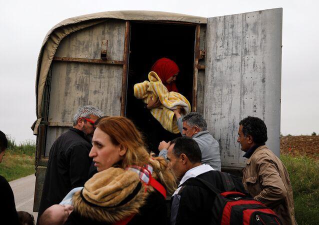 Meriç Nehri'ni geçip Yunanistan'a ulaşan Suriyeli sığınmacıları Yunan polisi kamyonlarla kamplara taşıyor.