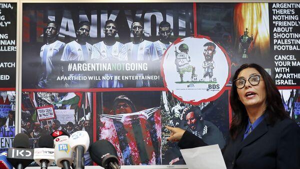 İsrail Kültür ve Spor Bakanı Miri Regev, boykot kampanyasının bir İsrail askerinin topu ayağının altında gasp edip Messi'yi oynatmazken gösterdiği karikatürü ve bir protestocunun kırmızı boya sürülmüş Arjantin formasını yırttığı fotoğraf üzerinden 'terör' suçlamasında bulundu. - Sputnik Türkiye