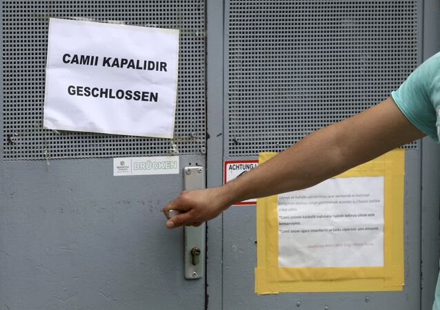 A man tries to open the door of a closed mosque in Vienna, Austria, Friday, June 8, 2018. The mosque is on of the seven mosques which the Austrian government said it's closing and plans to expel imams in a crackdown on political Islam and foreign financing of religious groups.