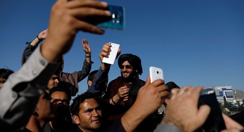 Kabil'deki bayramlaşmada Afgan siviller Taliban militanlarıyla özçekim yaptı.
