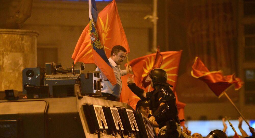 Birleşik Makedonya Partisi'nin lideri Yanko Baçev, Üsküp'te parlamento binası önünde ülkenin isminin değiştirilmesine karşı yapılan protestolarda Rusya bayrağı ve Makedonya'nın 1992-1995 yılları arasında kullandığı eski bayrağıyla zırhlı polis aracının üzerine çıktı