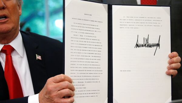 U.S. President Donald Trump displays an executive order on immigration policy after signing it in the Oval Office at the White House in Washington, U.S., June 20, 2018. - Sputnik Türkiye