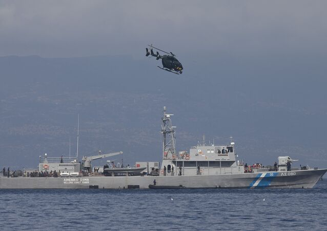 A small inflatable dinghy with a suspected smuggler on board is stopped by a Greek coastguard patrol boat, carrying migrants rescued at sea, as a helicopter from the European border control agency Frontex flies overhead, off Greece's eastern Aegean Sea island of Lesbos on Thursday, Sept. 24, 2015