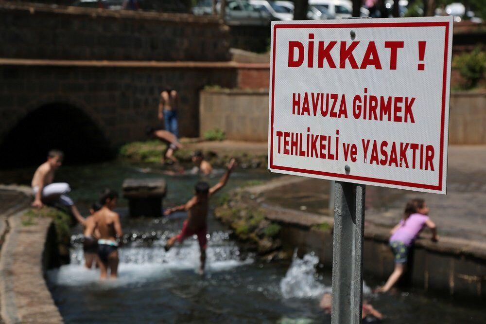 Diyarbakır'da sıcaktan bunalan çocuklar, süs havuzlarına girerek serinliyor.