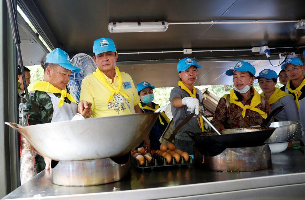 Tayland Başbakanı kurtarma görevlileri ve gönüllüler için kurulan mobil mutfakta yemek de hazırladı.