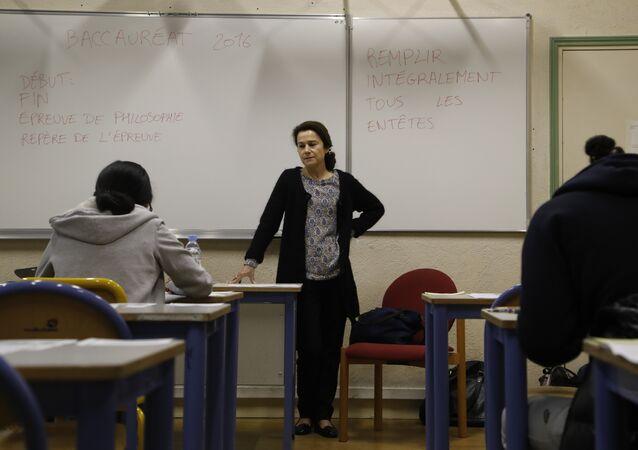 A teacher monitors (C) as High school students at the Charlemagne High School (Lycee Charlemagne) in Paris
