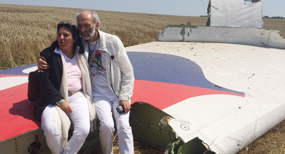 Jerzy Dyczynski and Angela Rudhart-Dyczynski whose daughter, 25-year-old Fatima, was a passenger on Malaysia Airlines flight MH17, sit on part of the wreckage of the crashed aircraft in Hrabove, Ukraine, Saturday, July 26, 2014
