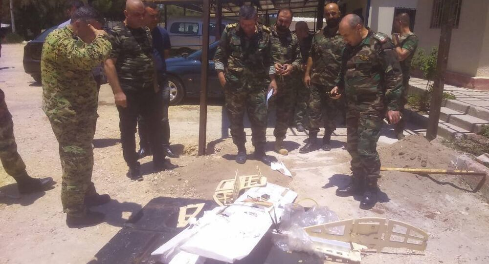 Syrian servicemen are seen near a downed drone