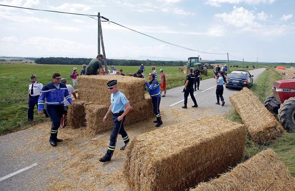 Polis memurları, saman balyalarını yoldan kaldırıyor.