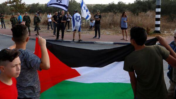 Batı Şeria'daki Rantis kontrol noktasında Tamimi'nin tahliyesini bekleyen Filistinliler, ellerinde bayraklarıyla İsraillilerle karşı karşıya. - Sputnik Türkiye