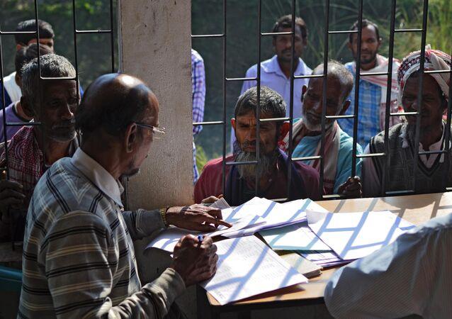 Hindistan'ın Assam eyaletinde Ulusal Vatandaşlık Kaydı'nın ilk taslağında isimlerinin yer alıp almadığını kontrol eden insanlar