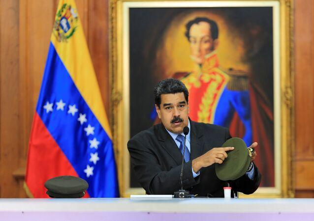 Venezüella Devlet Başkanı Nicolas Maduro saldırıda yaralanan askerlerden birinin şapkasını gösterirken