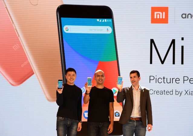 (L-R) Donovan Sung, director of product management and marketing at Xiaomi Global, Manu Jain, managing director of Xiaomi India, and global director of Android Partner Programs Jon Gold hold the newly launched Xiaomi Mi A1 smartphone at a function in New Delhi on September 5, 2017
