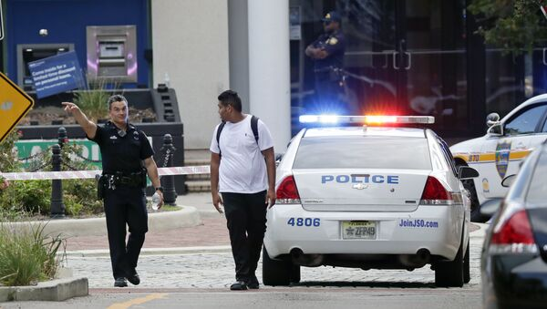A police officer directs a pedestrian away from a blocked-off area near the scene of a mass shooting at Jacksonville Landing in Jacksonville, Fla., Sunday, Aug. 26, 2018. - Sputnik Türkiye