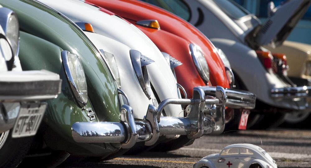 A Volkswagen Beetle toy is seen in front of Beetle cars during celebrations of the National day of the Beetle in Sao Bernardo do Campo in this January 23, 2011 file photo. Volkswagen is expected to release Q2 results this week.